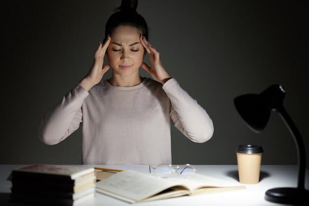 Jovem mulher bonita usa camisa casual, trabalhando à noite
