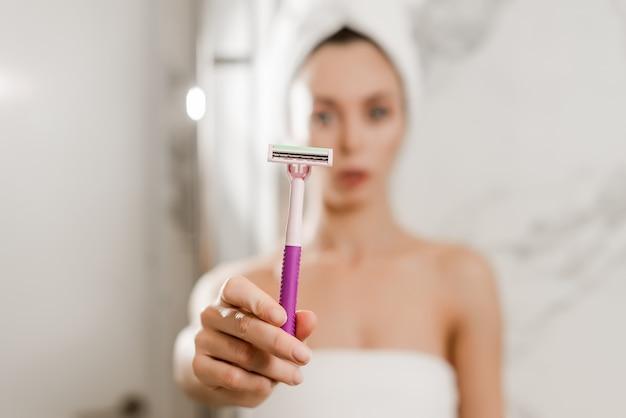 Jovem mulher bonita usa lâmina de barbear para biquíni envolto em toalhas no banheiro, navalha em foco