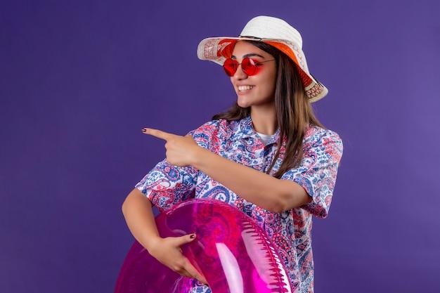 Jovem mulher bonita usando chapéu de verão e óculos de sol vermelhos, segurando o anel inflável, apontando com o dedo indicador para o lado, sorrindo alegremente sobre a parede roxa