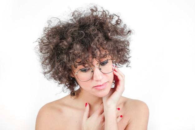 Jovem mulher bonita usando óculos contra fundo branco