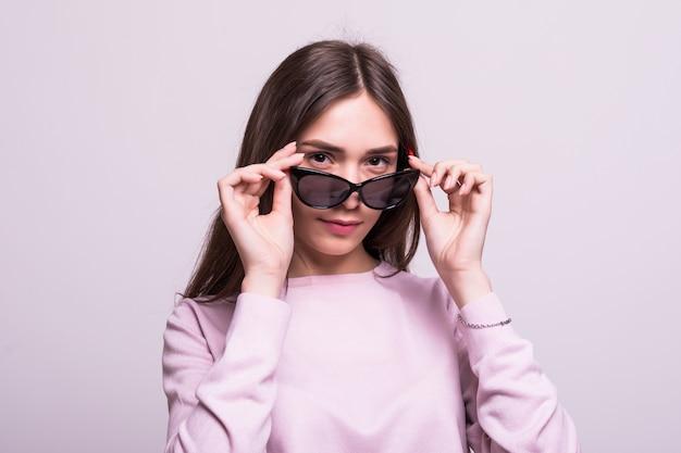 Jovem mulher bonita usando óculos escuros sobre um fundo branco