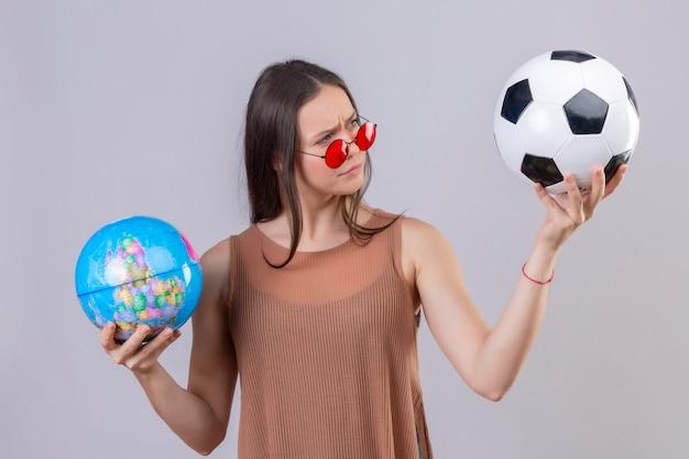 Jovem mulher bonita usando óculos escuros vermelhos segurando uma bola de futebol e um globo olhando para a bola com uma expressão suspeita em pé sobre um fundo branco