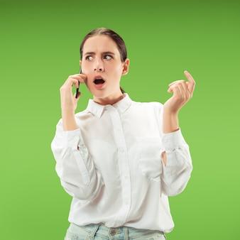 Jovem mulher bonita usando telefone celular na parede de cor verde. conceito de emoções faciais humanas. cores da moda