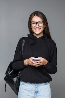 Jovem mulher bonita usando telefone inteligente isolado na parede cinza