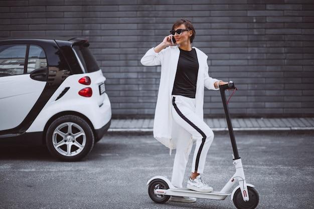 Jovem mulher bonita vestida de scooter de equitação branca