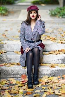 Jovem mulher bonita vestindo casaco e boné de inverno, sentado nos degraus cheios de folhas de outono