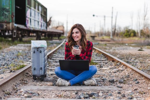 Jovem mulher bonita vestindo roupas casuais, sentado na estrada de ferro com mala, laptop e um mapa, ela está sorrindo e segurando uma xícara de café. estilo de vida ao ar livre. conceito de viagens.