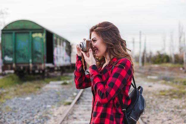 Jovem mulher bonita vestindo roupas casuais, tirando uma foto com uma câmera vintage.