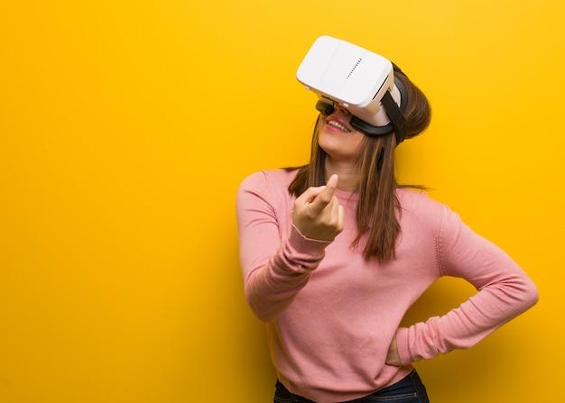 Jovem mulher bonita vestindo uma realidade virtual googles convidando para vir