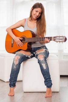 Jovem, mulher bonita, violão jogo