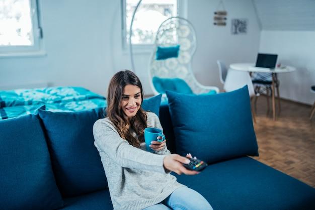 Jovem mulher bonito que olha a tevê. segurando uma caneca e controle remoto enquanto está sentado no sofá.