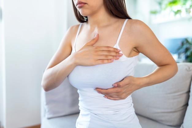 Jovem mulher branca apalpando o seio sozinha, que se preocupa com o câncer de mama. conceito de saúde e câncer de mama