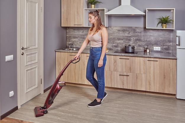 Jovem mulher branca aspira o chão da cozinha usando um aspirador de pó tipo stick vertical sem fio.