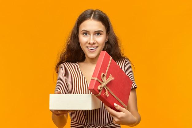 Jovem mulher branca com cabelo comprido e cacheado sorrindo e segurando um presente aberto