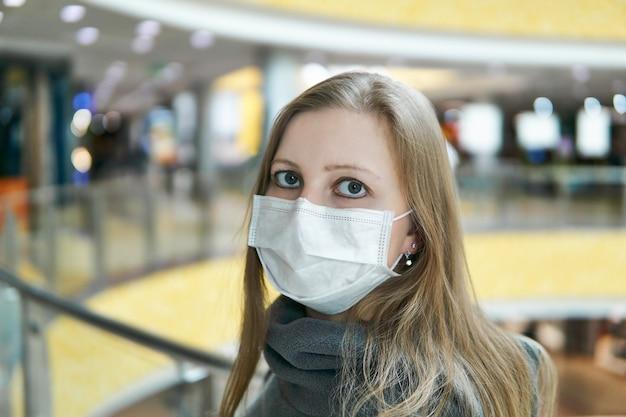 Jovem mulher branca com máscara cirúrgica em um espaço público