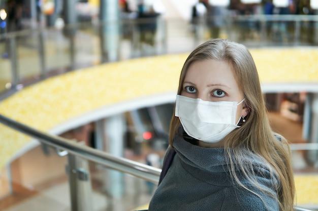 Jovem mulher branca com máscara médica em um espaço público