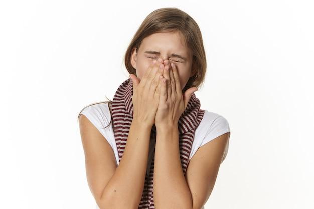 Jovem mulher branca com resfriado e coriza, espirrando ou tossindo, sendo alérgica, cobrindo o rosto com as mãos, usando lenço quente. conceito de rinite, doença e alergia