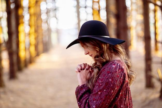 Jovem mulher branca com um elegante chapéu preto rezando na floresta cênica, clima de outono