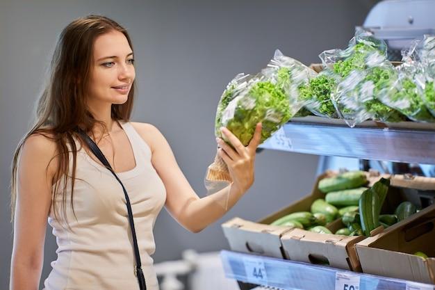 Jovem mulher branca escolhe salada no supermercado