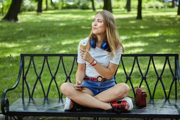 Jovem mulher branca está comendo sorvete em um parque público.