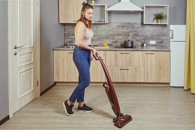 Jovem mulher branca fazendo arrumação na cozinha usando aspirador de pó vertical sem fio ou vassoura elétrica.