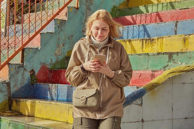 Jovem mulher branca usa smartphone durante passeio turístico pelas ruas de istambul, na turquia.