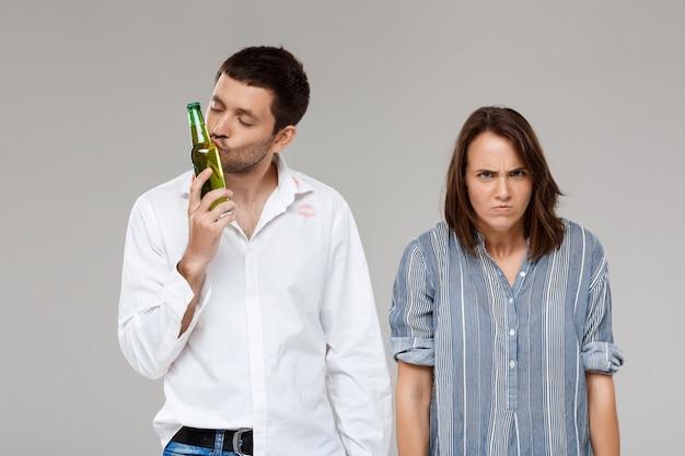 Jovem mulher brigando, irritando-se com o marido bêbado sobre parede cinza