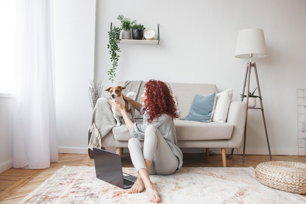 Jovem mulher brincando com seu animal de estimação. fêmea e seu cachorro interior. um proprietário e seu animal de estimação em casa se divertindo. jack de treinamento mulher russel terrier para executar comandos.