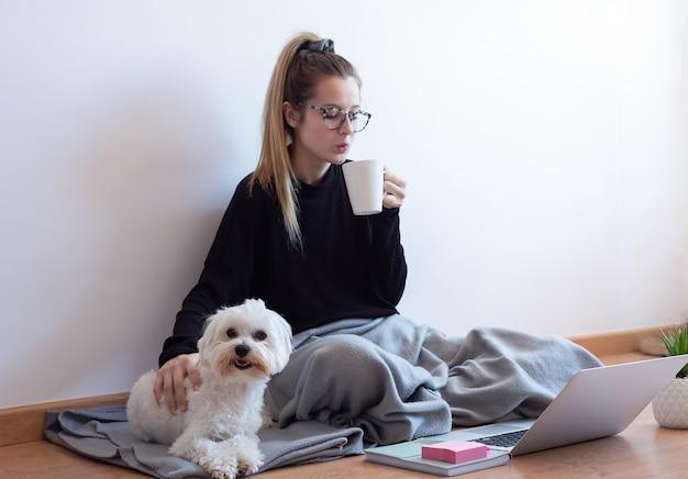 Jovem mulher brincando com seu cachorro e tomando café em casa