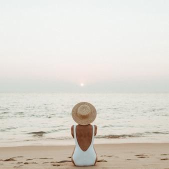 Jovem mulher bronzeada vestindo um lindo maiô branco com um chapéu de palha está sentada e relaxando em uma praia tropical com areia branca e está assistindo o pôr do sol e o mar