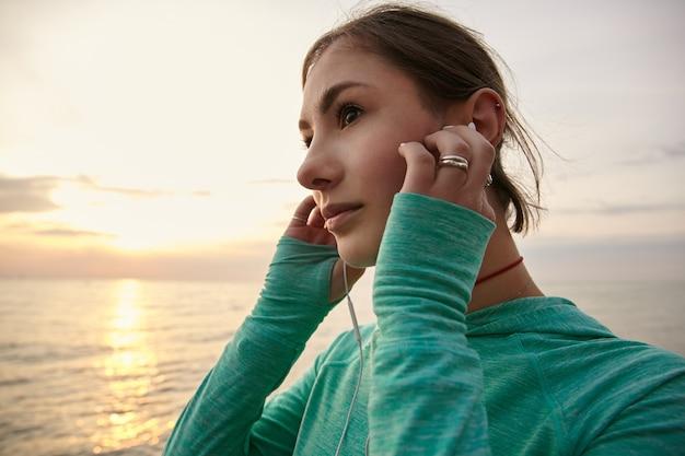 Jovem mulher calmante à beira-mar por do sol, ouvindo música favorita em fones de ouvido. e olhando para o pôr do sol.