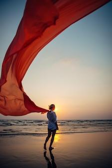 Jovem mulher caminha ao longo da praia do mar, segurando o pano longo vermelho ao vento.