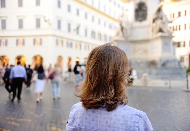 Jovem mulher caminha na praça em roma.