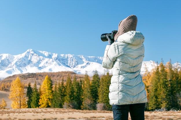 Jovem mulher caminhadas tira fotos em uma câmera de montanha. mulher blogueiro tirando foto de câmera de montanhas de pico de neve.