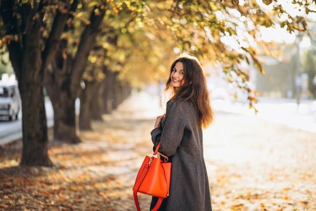 Jovem mulher caminhando em um parque de outono