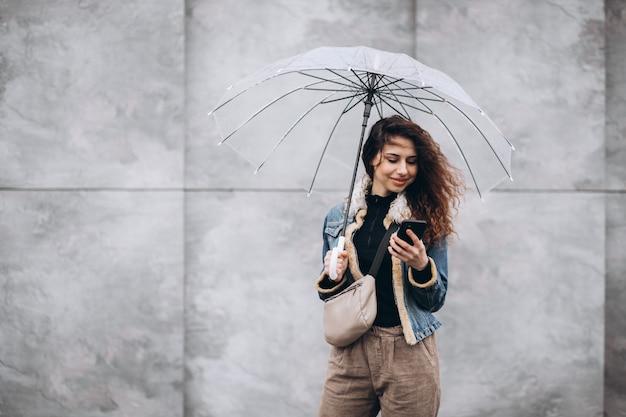 Jovem mulher caminhando na chuva com guarda-chuva