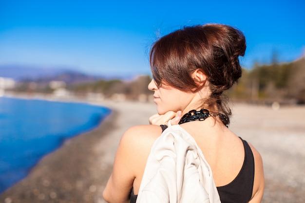 Jovem mulher caminhando na praia em dia ensolarado de inverno sozinho