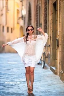 Jovem mulher caminhando pelas ruas desertas da europa.