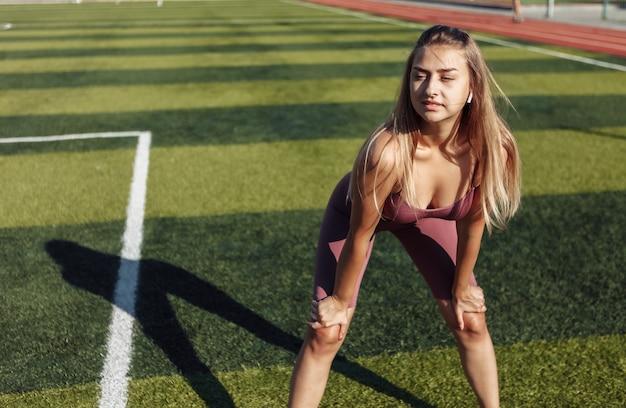 Jovem mulher cansada em roupas esportivas no estádio. dia de sol brilhante. treinamento ao ar livre