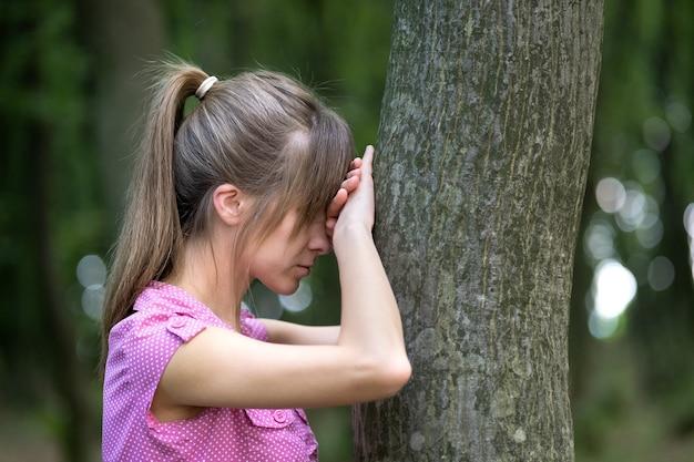 Jovem mulher cansada, inclinando-se para um tronco de árvore na floresta de verão.