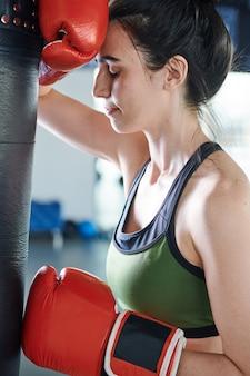Jovem mulher cansada ou estressada usando luvas de boxe em pé ao lado do saco de pancadas durante o treino na academia