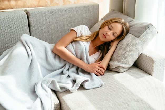 Jovem mulher cansado que dorme no sofá na sala de visitas em casa. concep de lazer