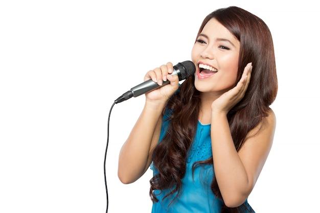 Jovem mulher canta segurando um microfone, isolado
