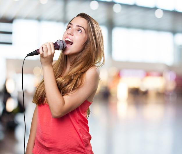 Jovem mulher cantando com um microfone no fundo branco