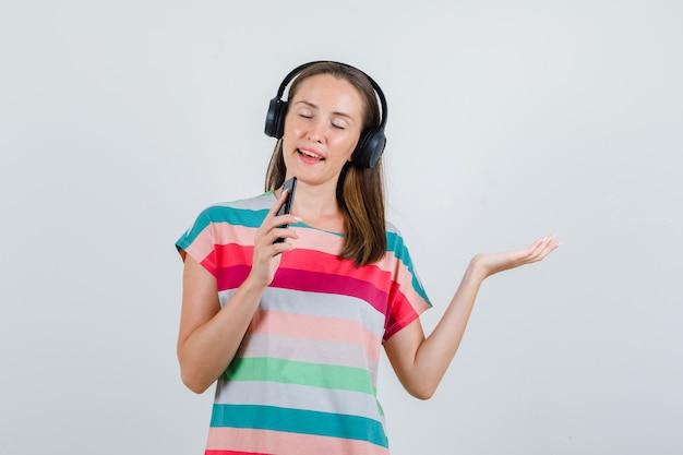 Jovem mulher cantando no celular como microfone em t-shirt, fones de ouvido, vista frontal.