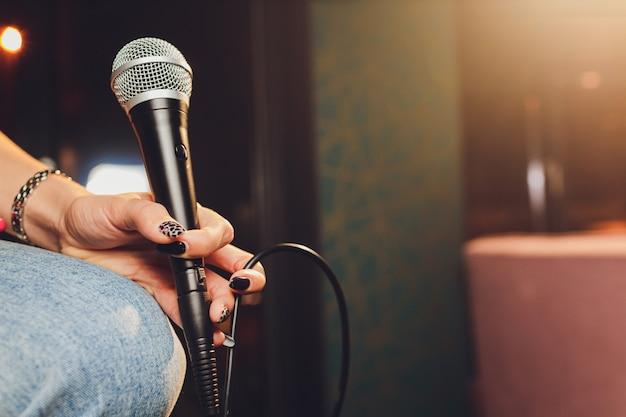 Jovem mulher cantando no karaokê e segurando um close-up do microfone.