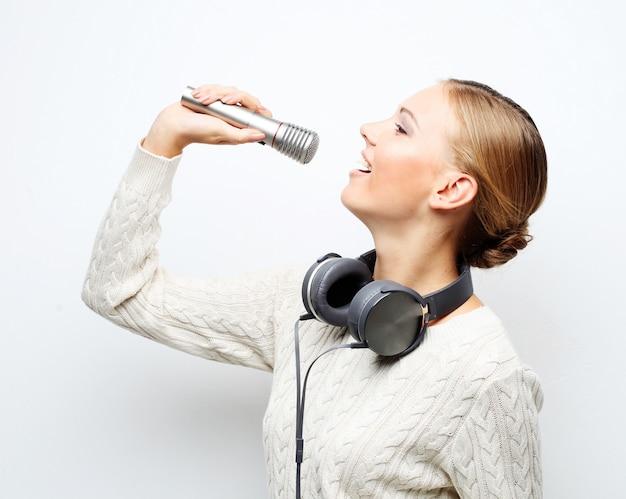 Jovem mulher cantando no microfone com fones de ouvido