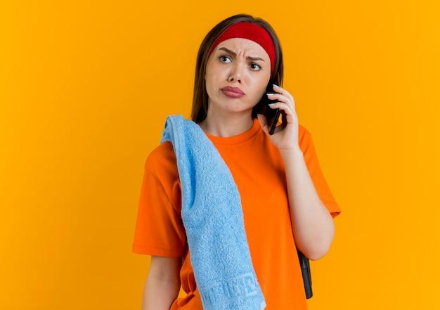 Jovem mulher carrancuda e esportiva usando bandana e pulseiras com corda de pular e toalha nos ombros falando no telefone, olhando para o lado