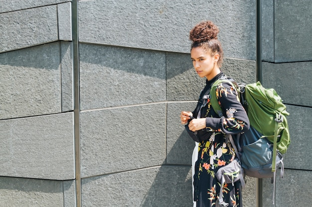 Jovem mulher carregando mochila em pé perto da parede ao ar livre
