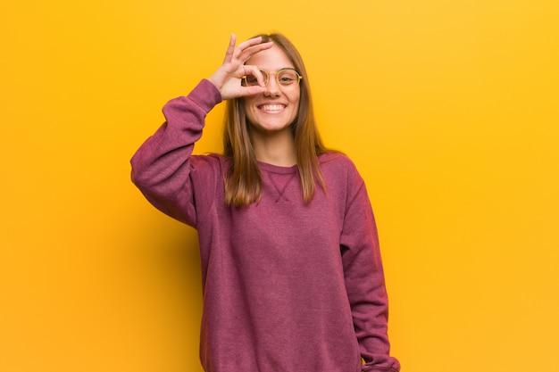 Jovem mulher casual confiante fazendo okey gesto no olho